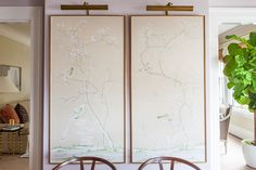 A pair of framed panels of chinoiserie paper -- i always love this sort of formatting/framing/lighting for art. there are a number of walls in my great room where this would be a lovely treatment.