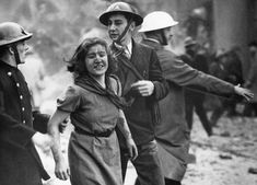 This smiling girl, dirtied but apparently not injured, was assisted across a London street on October 23, 1940, after she was rescued from the debris of a building damaged by a bomb attack in a German daylight raid. (AP Photo)
