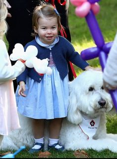 Princess Charlotte looks as happy as her great grandmother is with a dog.