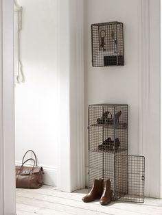 Druciane szafki na klucze i buty wnoszą do białego skandynawskiego przedpokoju industrialny styl. Dla złagodzenia ich surowego wyglądu w dalszej części pomieszczenia zawieszono lustro w rzeźbionej ramie. Na tle ściany w tym samym kolorze subtelnie dekoruje wnętrze.