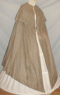 "1860s cotton print cape of gray and white. Hemline has a black and gray checked pattern. Wide shawl style collar and center back bow. All hand sewn and is unlined. One hook closure at neckline. Shoulders: 16""; Front length: 47""; Back length: 41"