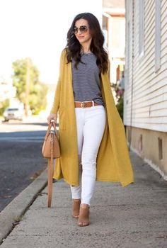 Conjunto cardigan amarillo, camiseta azul marino a rayas, pantalones blancos, botas beis, bolso beis y gafas marrones