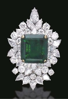 A SPECTACULAR EMERALD AND DIAMOND BROOCH Centering upon a square-cut emerald, weighing approximately 29.67 carats, within a circular-cut and pear-shaped diamond cluster surround, enhanced by a similarly-set detachable base, mounted in platinum and gold