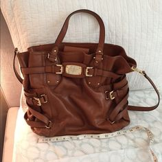 Micheal Kors satchel Beautiful Michael Kors satchel in chestnut brown with criss cross straps on the sides. Can be used as crossbody or satchel. This item has minor scratch on exterior otherwise in very good condition. Please feel free to make a reasonable  offer  Happy poshing! Michael Kors Bags Satchels