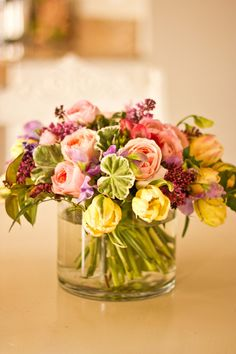 Arrangement of peach garden roses, yellow tulips and variegated geranium leaf