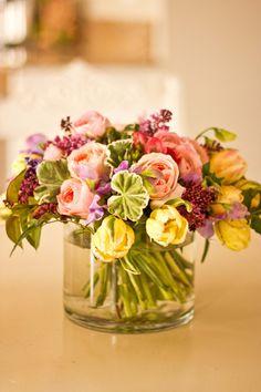 Arrangement of peach garden roses, yellow tulips and variegated geranium leaf