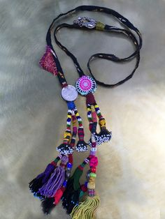 Kinship Stories: Tribal art necklace whose base is made with vintage Afghani embroidery. Tassels are vintage Uzbek and come from old headdresses. The coins are Iranian, the mixed silver Yemeni and the fabric amulets Thai (circular) and Afghani (triangular). This is a one-of-a-kind handmade piece.