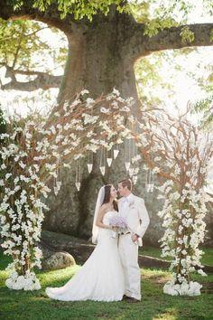 mariage conte de fée, arche mariage en branches décorée de fleurs et de suspensions