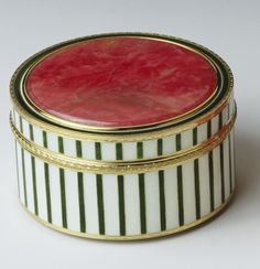 A circular box, hinged at the back, the straight sides have alternating green and white guilloché enamel vertical stripes, the cover and base are mounted with circular panels of rhodonite, the two-colour gold mounts have foliate trail rim. The design for this box has recently come to light in the published album from Henrik Wigström's workshop.    Gold mark of 72 zolotniks (1908-17); Fabergé in Roman letters; English import marks