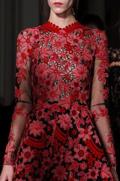 exquisite red floral applique on black tulle.  Long sleeves, and high neck around the base of the throat