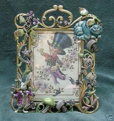 "Kirks Folly ALICE IN WONDERLAND Cheshire Cat Frame (06/15/2008)his is the Alice in Wonderland Fantasy Frame and it is loaded with incredible detail, they have used the actual true sized pins as decorations on this frame. It measures 7"" tall by 5-1/2"" wide and will hold a photo which measures 4-1/2"" by 3"". It is signed on the back with the oval Kirks Folly signature id and is done with vibrant enamelling, follydust rainbow glitter and rainbow Aurora Borealis crystals."