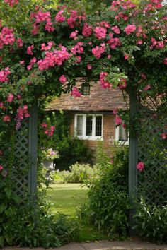 view of a lovely cottage thru a rose covered arbor