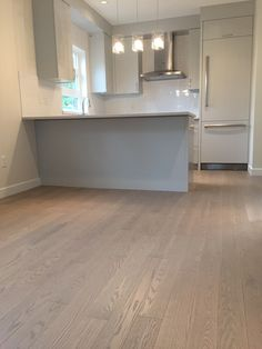 Beautiful kitchen featuring Lauzon's Nostalgia wire brushed hardwood flooring from the Authentik Series. This gray flooring features the exclusive air-purifying technology called Pure Genius technology. Project realized by Trasolini Chetner Construction. #interiordesign #hardwoodfloor #artfromnature