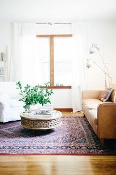 A Beautifully Decorated Rental | lark & linen. Rug, round bamboo/rattan coffee table, plants, camel couch.