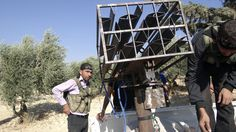 Free Syrian Army fighters stand next to a home-made rocket launcher in Sermeen near Idlib, October 17, 2012.
