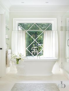 Sun filled bathroom features an oval freestanding tub paired with a vintage tub filled placed under window dressed in white sheer cafe curtains flanked by nook filled with stacked glass shelves above a built-in cabinet to the left and a seamless glass walk-in shower to the right.