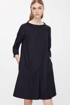 Made from soft unlined wool, this has A-line dress has a wide neckline and narrow standing collar. Designed to pull on, it has 3/4 sleeves, in-seam pockets and a single pleat on the front.