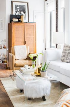 Cozy living space with am acrylic coffee table, a camel leather armchair and a white sofa