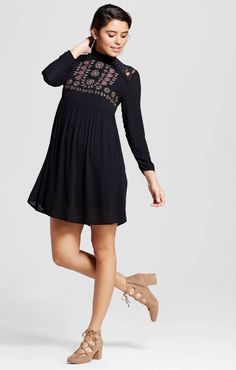1e937f995cf A long-sleeved dress with embroidery and lace detailing.