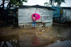 Credit: Kieran Doherty A young girl holds her parasol as she walks through a slum area in Monrovia. Fresh rain water causes the slums to qui...