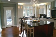 Sink wall of kitchen with transoms and lighted upper cabinets.