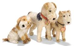 THREE STEIFF ARTIFICIAL-SILK DOGS, an unlisted seated Spaniel(?), white and light brown, brown and black glass eyes, black stitching, swivel head, inoperative squeaker, red collar and FF button with remains of yellow cloth tag, 1940s --7in. (17.5cm.) high; and two Fox Terriers, one with blank button and chest tag --11in. (28cm.) long and one with grey painted FF button and cream card ear tag, chest tag --9in. (23cm.) long (some wear)