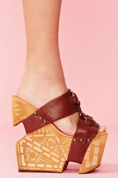 Ah-mazing brown leather platform wedges featuring a buckled cutout upper with brass studs. Cutout wooden wedge heel with etched detailing. Genuine leather lining, cushioned insole. Perfect paired with a crochet dress and wide-brim hat! By Jeffrey Campbell.