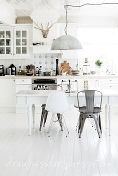 Stylish Scandinavian style dining area with stylish metallic features enhancing a crisp white backdrop.