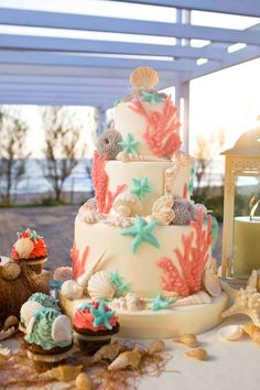 Lovely ocean-themed wedding cake.  Soft white, aqua and coral.  Perfect for a beach wedding :-)