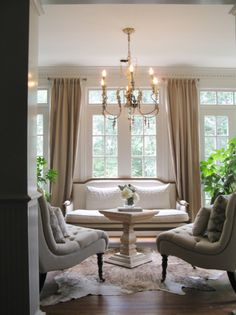 living rooms - Benjamin Moore - China White - french living room, french living room design, candle chandelier, cloud white, cloud white walls, cowhide rug, french settee, slipper chairs, tufted slipper chairs, wall of french doors, wall of french doors and transom windows,