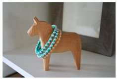 DIY turquoise pearl braclets on the neck of a Swedish horse