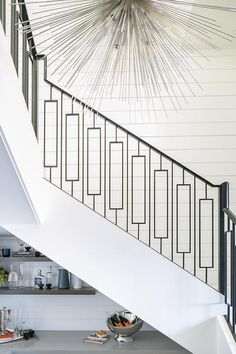 A silver sputnik chandelier illuminates a white shiplap wall lining a white staircase contrasted with a wrought iron handrail and spindles. Iron Handrails, Wrought Iron Staircase, White Staircase, Wrought Iron Spindles, Staircase Railing Design, Iron Stair Railing, White Shiplap Wall, Entrance Foyer, Modern Stairs