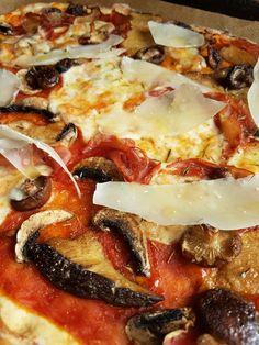Homemade pizza met bospaddenstoelen, mozzarella en schilfers parmigiano