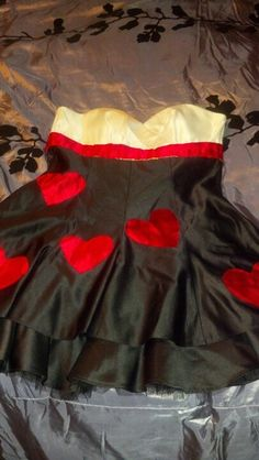 "Homemade queen of hearts costume. I used red satin and cut out hearts and a ""sash"" applied them to a value village salvaged prom dress with stitch witchery them hand stitched the edges for a more finished look"