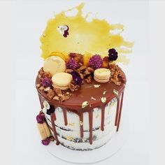 Belgian chocolate cake filled with salted caramel and vanilla buttercream, topped with salted caramel macarons, candied walnuts, toffee shard and edible flowers
