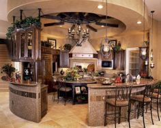 Wow!!! I absolutely love the layout. Still has an island for cozy dining spot for two and casual conversation or clear it out for serious prep work. Love the open layout that lets you see and be seen. Love the additional seating around the outside. You could hand some neat racks from the wooden beams. Just found my favorite kitchen layout to date!!!