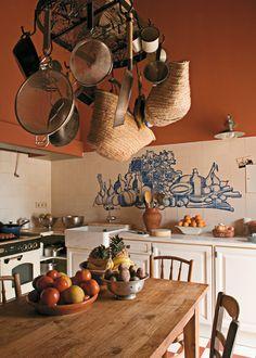 De efecto artesano, sobre el azulejo hecho a mano de la pared de esta cocina se ha encargado la realización de un mural pintado a mano con motivos gastronómicos.