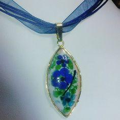Pendentif romantique en émail décoré de petites  fleurs bleues sur fond d'émail blanc opale