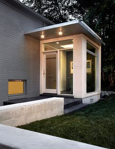 ceiling light near concrete garden wall alongside glass front door alongside grass including gray as well lawn amidst minimal next to overhang among painted brick alongside tile entry including transom window as well vestibule Sas Entree, Modern Front Porches, Modern Entry, Building A Porch, Front Door Design, Entrance Design, Glass Front Door, Glass Doors, Glass Porch