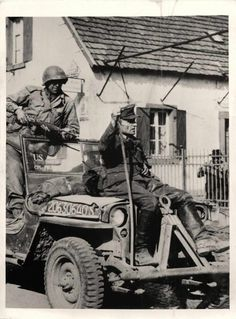 1945- German prisoner rides atop jeep enroute to nearest prisoner of war cage after his capture by U.S. 7th Army troops.