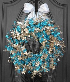 Newest original design and wreath creation!  Blue and silver sparkling eucalyptus stems surround the grapevine wreath, then adorned with a wide, wired, glittering silver bow.