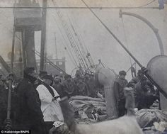 History In Pictures ‏- Rare photo shows a priest praying over Titanic victims before they are buried at sea. 1912