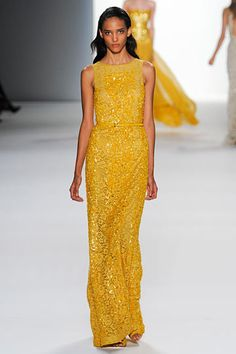 ELIE SAAB: Spring 2012 RTW...the designer continues the themes of his show from the beginning in an all beige lineup to an array of vivid colors which we see here included a bright canary yellow, as well as an emerald green and electric blue to follow. Here we see the elegant evening look of sequins, paired with the lace like pattern of the previous dress and again, emphasis on the waistline
