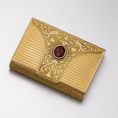 GOLD AND CARNELIAN INTAGLIO BOX, LATE 19TH CENTURY. The engine-turned rectangular box decorated on the hinged lid with a panel of scrollwork, the center accented with an oval carnelian intaglio carved in classical taste with a seated man and a swan, gross weight approximately 52 dwts., 3 1/8 by 2 ¼ inches.