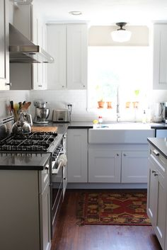 This gorgeous white kitchen includes Martha Stewart Dunemere Cabinetry in Picket Fence   From Handmaid Tales blog