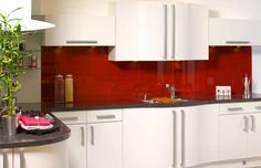 Red glass splashback with black benchtop and white cabinets