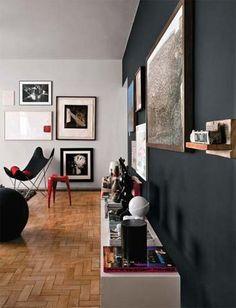 A parede pintada de preto fosco deixa o móvel branco e os quadro em destaque no apartamento dos publicitários Ângela e Marcone assinado pela arquiteta Andrea Buratto.
