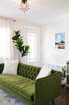 """The color of the sofa pairs so well with the art, which suggests """"road trip,"""" """"nature,"""" or """"camping."""" The two plants, too, enhance the notion of traveling to the woods. Well paired. #emotionaldesign #green #interiordesign #art #designwithnature"""