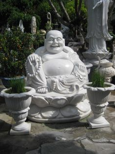 Laughing Buddha hand-carved of grey marble sits over 3 feet tall.