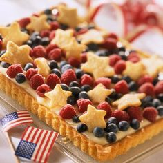 Top a fruit pizza with mini star-shaped sugar cookies for a patriotic treat. Recipe: http://www.bhg.com/recipe/tarts/red-white-and-blue-tart/